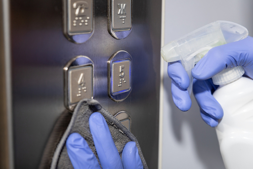 elevator cleaning service hands in blue rubber gloves holding microfiber cleaning cloth and spray bottle with sterilizing solution make cleaning and disinfection for good hygiene of elevator buttons. Prevention of coronavirus